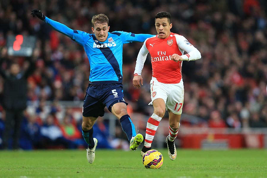 11 January 2015 - Barclays Premier League - Arsenal v Stoke City -- Alexis Sanchez of Arsenal in action with Marc Muniesa of Stoke City  Photo: Marc Atkins / Offside.