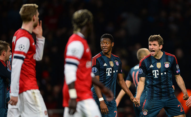 19 February 2014 - UEFA Champions League (RO16) - Arsenal v Bayern Munich - Thomas Muller of Bayern Munich celebrates his goal in front of Bacary Sagna and Per Mertesacker of Arsenal - Photo: Marc Atkins / Offside.